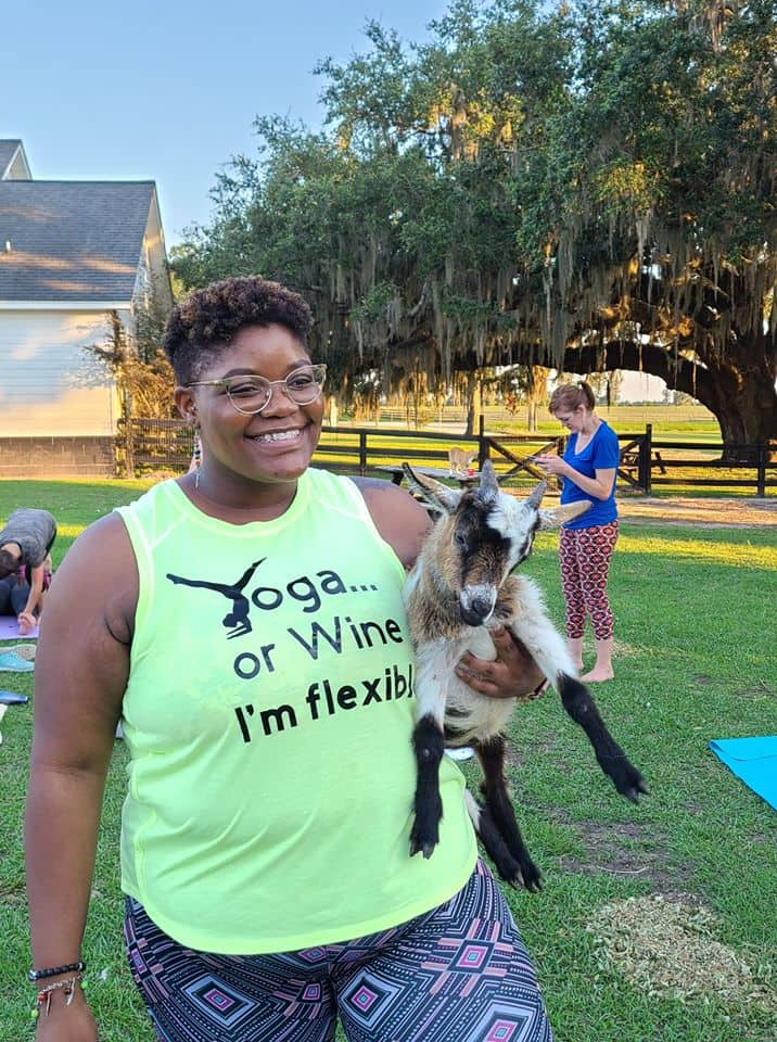 Yoga Class Valdosta GA. A photo of a woman holding a goat before yoga class